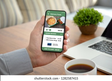 male hands holding phone with app delivery food on the screen above the table in the office