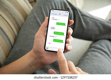 male hands holding phone with app messenger on the screen sofa in room