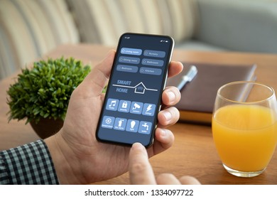 male hands holding phone with app smart home on the screen above the table in office