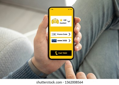 male hands holding phone with call taxi app on the screen