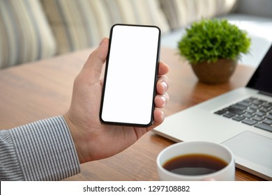 male hands holding phone with isolated screen above the table in the office