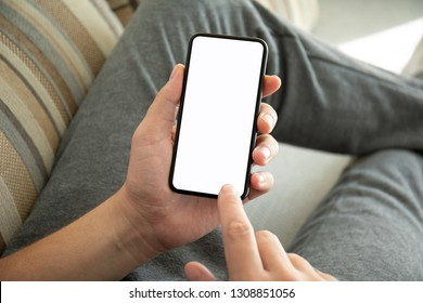 male hands holding phone with isolated screen on the sofa in the room