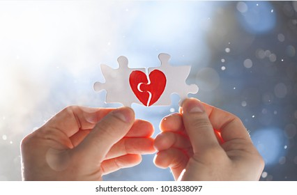 Male hands holding puzzles with red heart. Love concept