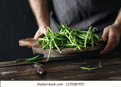 Male hands holding raw green bean on wooden cutting board on dark background. Healthy, vegetarian food concept