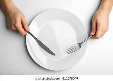 Male hands holding silver cutlery over plate, isolated on white
