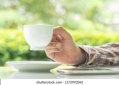 Male hands holding smart phone and cup of coffee on the table  outdoor with blurred green plant background