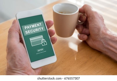 Male hands holding a smartphone with payment security concept and a cup of coffee