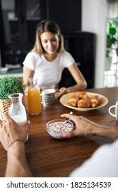Male hands holding spoon, bowl of cereals and a bottle of milk. His girlfriend is holding coffee mug