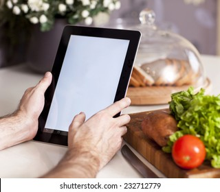 male hands holding a tablet at the kitchen table