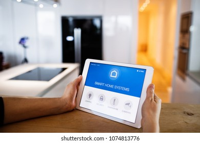 Male hands holding a tablet with smart home screen.