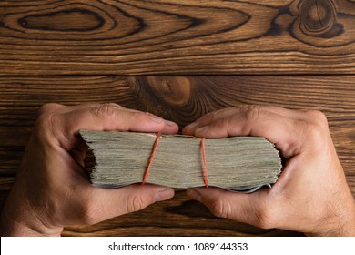 Male hands holding a thick wad of money tied with rubber bands over a rustic wood table viewed edge on from above with copy space