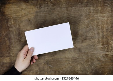 male hands holding a white blank sheet of paper on the background of wooden texture table