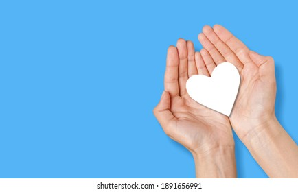 Male hands holding white heart shape. Charity and kindness concept.