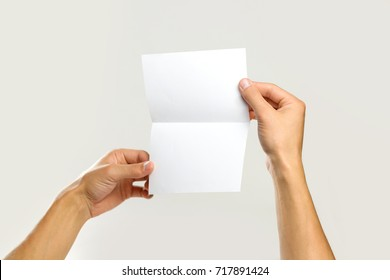 Male hands holding a white sheet of paper. Isolated on gray background. Closeup.