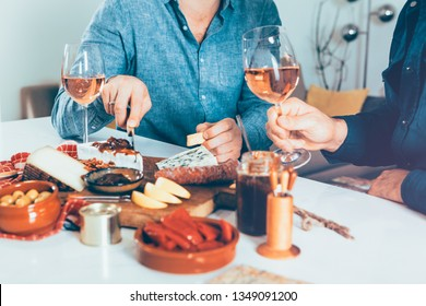 male hands holding a wineglass and cutting cheese  on table laden with food