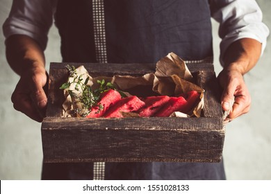 Male hands holding wooden bord with slieces of juicy ripe watermelon, that are stacked on top of each other, above the white table. Top-side view. Vertical
