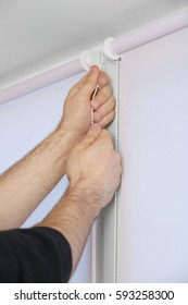 Male hands installing roller blinds on window