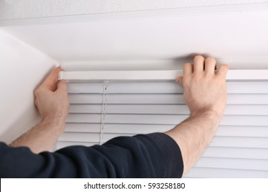 Male hands installing window blinds