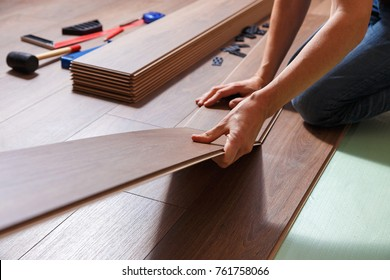 Male hands installing wooden laminate flooring. On the floor are different carpenter's tools.