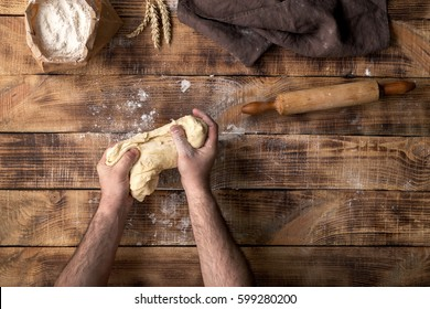 Male hands knead the dough on a wooden table, top view