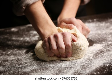 Male hands kneading dough on sprinkled with flour table, closeup