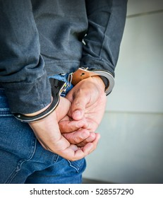 Male hands locked in handcuffs, Outlaw's hands in handcuffs
