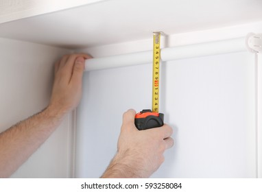 Male hands making window measurements
