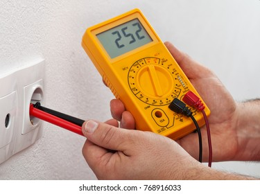 Male hands measuring voltage in electrical wall receptacle - closeup