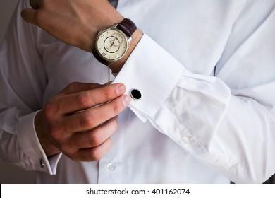 Männliche Hände auf weißem Hintergrund, ärmeliges Hemd mit Manschetten und Uhren, Nahaufnahme