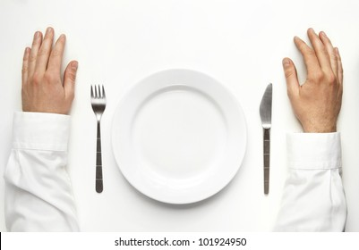 Male hands over the table waiting for dinner isolated on white. Between the two hands are plate, fork and knife.