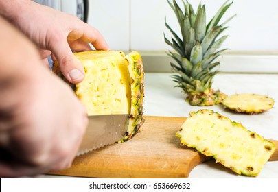 Male hands peeling fresh pineapple skin close up