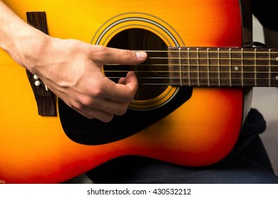 Male hands playing acoustic guitar, close up