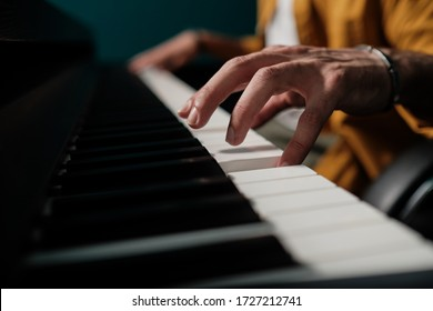 Male hands playing keyboard at the studio