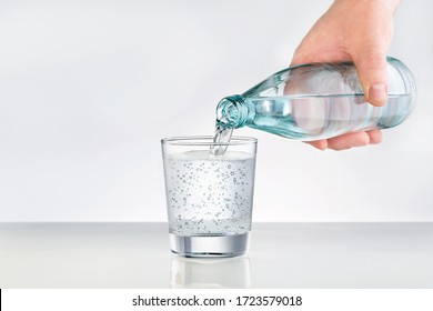 Male hands pouring bottled water into glass. Water glass with copy space. Mineral water for healthy lifestyle.