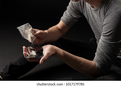 Male hands pouring cocaine out of package onto metallic plate. Misuse concept