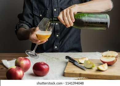 Male hands pouring premium cidre in wine glass above rustic wood table. Man pours a glass of vintage apple wine out of ice cold bottle