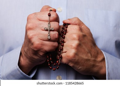 Male hands praying holding a beads rosary with Jesus Christ in the cross or Crucifix on black background. Mature man with Christian Catholic religious faith