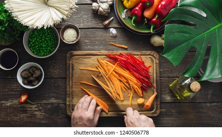 Male hands prepare vegetarian thai noodles on dark wooden table in home kitchen top view
