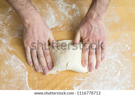 Male hands preparing dough for pizza on table in kitchen closeup, Man kneading raw dough on table at bakery, prepare pastry hand topping, Making dough, Knead, Bread, Cooking Process, Baking concept