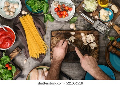 Male hands preparing ingredients for pasta on a wooden table, top view