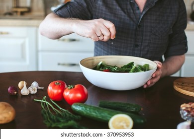 male hands preparing vegetarian salad in the kitchen