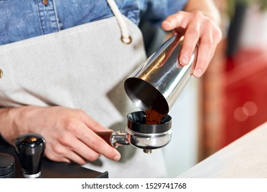 Male hands puts ground coffee into tamper at bar counter, Barista takes order to make cup of hot aromatic cappuccino for friendly guests, close up