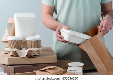 Male hands putting take-out food container into paper bag, close-up. Coffee cups in holder, several pizzas, light grey background. Delivery.