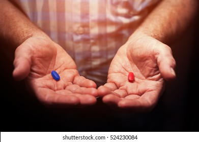 Male hands with red and blue pills, closeup