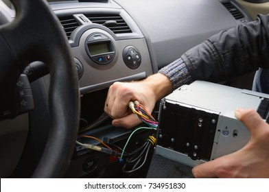 Male hands remove audio system from car dashboard. Automobile receiver disconnecting and removing