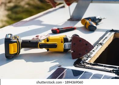 Male hands repair caravan motor home roof.