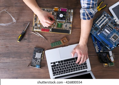 male hands repairing computer details and using laptop on wooden table top view