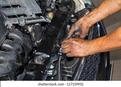 Male hands repairing engine