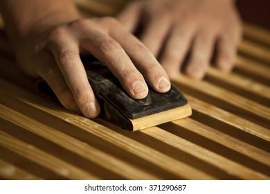Male hands sanding wooden slats.
