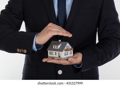 Male hands saving small house with a roof. Insurance and security concept.